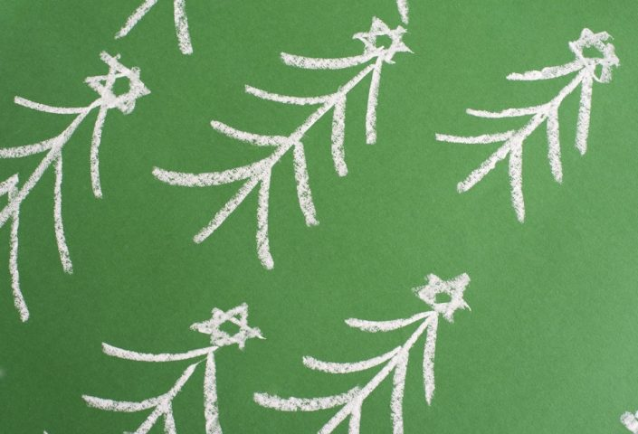 Chalk hand-drawn Christmas trees forming a diagonal pattern on a green chalkboard for a festive Xmas background